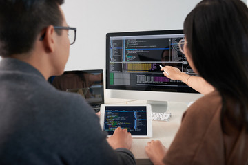 Crop back view of man and woman sitting at computer and discussing software code displayed on black monitor screen, man holding tablet with code in hands