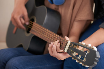 Crop view of couple in casual clothes sitting together, female holding acoustic guitar and male embracing her showing how to play on blurred background