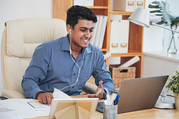 Cheerful Indian man working and communicating with laptop in office