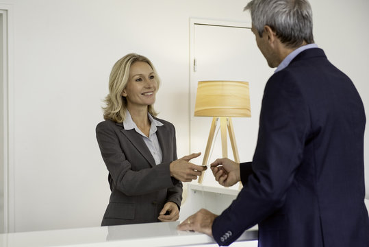 Receptionist receiving business card from businessman