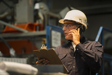 Factory worker using mobile phone in factory