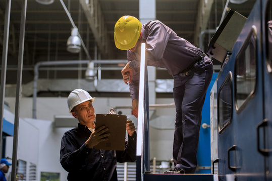 Factory workers with clipboard in factory