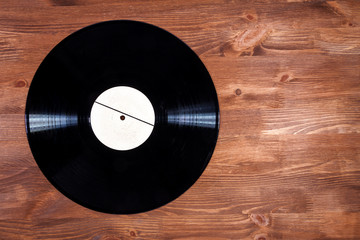 Black color vinyl record on brown wooden background