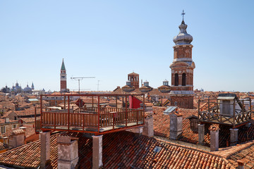 Elevated view of Venice roofs with typical altana balcony and San Marco bell tower in summer, Italy