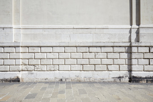 Empty tiled stone sidewalk and ancient white wall with molding