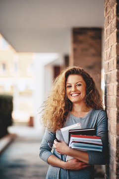 Girl standing against the brick wall and holding book.
