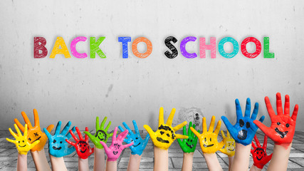 """angemalte Kinderhände und die Nachricht """"Back to school"""" in bunten Farben"""