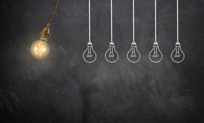 Glühbirne als Pendel stößt andere gezeichnete Glühbirnen an