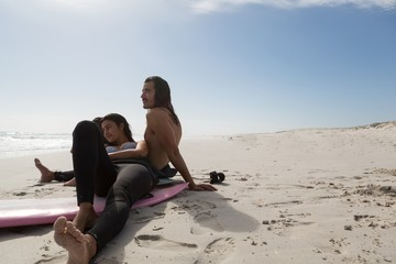 Surfer couple relaxing in the beach