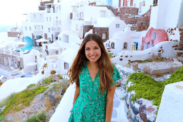 Santorini travel tourist woman visiting famous white village of Oia. Smiling tanned girl in green dress climbs the stairs in Santorini, Cyclades, Greece. European summer holidays concept.