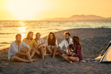Young friends with guitar at beach. friends relaxing on sand at beach with guitar and singing.