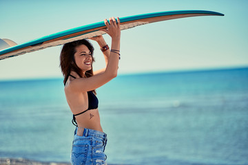 Surf girl go to surfing- women holding a surfboard.