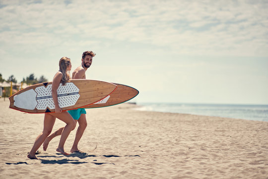 Happy couple surfers going together to surf at the beach .