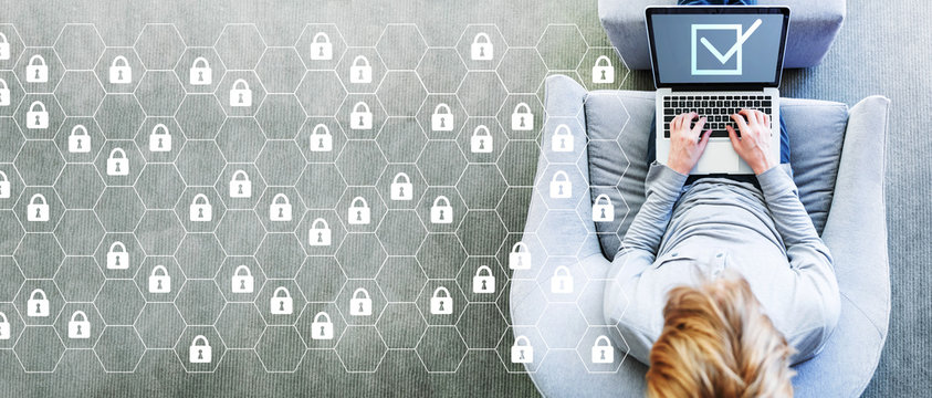 Cyber security concept with man using a laptop in a modern gray chair