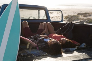 Couple relaxing in a pickup truck at beach