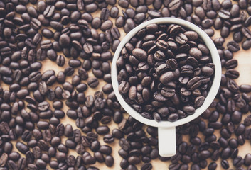 Close up of white coffee cup full of coffee beans background with copy space