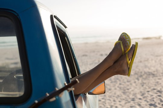 Woman relaxing with feet up in a pickup truck