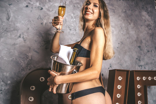 Pretty lady with big attractive ass smiling and holding a bottle and a glass with expensive champagne. Elegant model in fashionable lingerie. Bachelor Party Concept