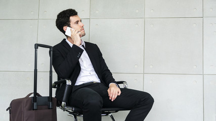 business man is sitting on chair waiting for business trip travel with suitcase and calling smartphone