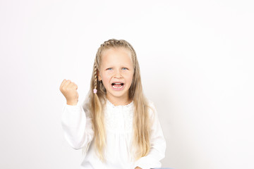 Portrait of beautiful, funny and angry four year old little girl raging with fists, showing knuckles, frowning. Female child screaming, behaving capriciously, crying. Background, copy space, close up.