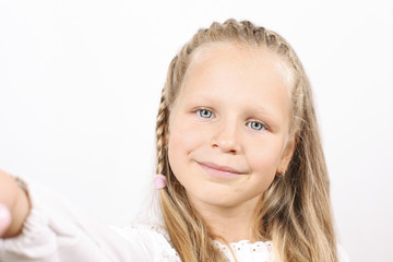 First person view of cute blonde four year old girl with funny pigtail and beautiful blue eyes taking selfie on smartphone. Childhood & technology concept. Adorable little child. Copy space background