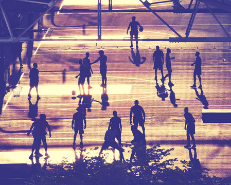 Street basketball players silhouettes at sunset, color toning applied, New York City, USA.