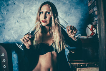 Beautiful blond girl stands and holds two empty glasses. Model is upset and sad. Woman experiences feelings of shame and weakness. Concept of the end of the holiday and overdose
