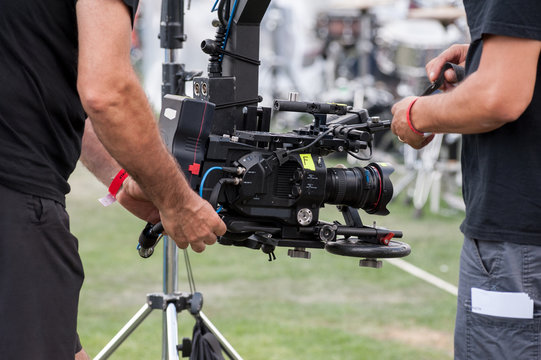 Technical camera operators set professional video camera on a large crane jib arm.