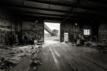 Black and white image of a deserted factory building.