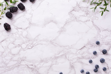 Marble background with fresh blueberries and blackberries with green plants