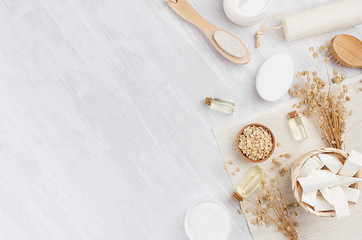 Traditional natural rustic spa white cosmetics products and beige bath accessories on light wood...