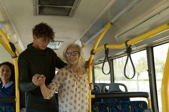 Young man helping senior woman in the bus