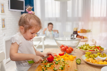 Little girl slices tomatoes for a salad, concept of cooking.