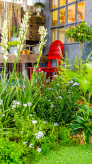 Relaxing area in cozy home garden on summer./ Relaxing area with red chair and garden object decoration in cozy home flower garden on summer.