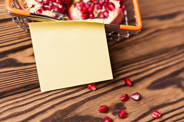 One blank square paper before full metal market basket of halves of red ripe fresh pomegranate and scattered seeds on old brown weathered rustic planks