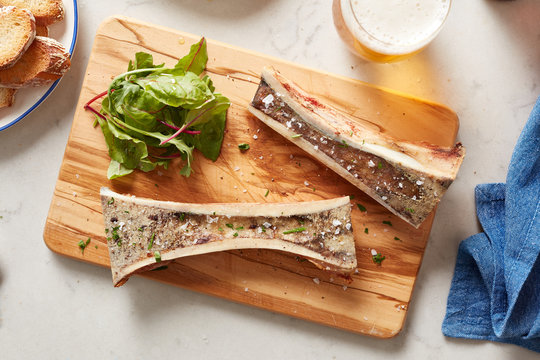 Top view of marrow bones with lettuce on board.