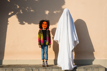Girl in pumpkin mask holding hand of ghost in the street.
