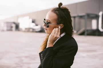 Beautiful young woman listening to music on headphones in city