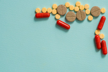 Yellow pills and capsules on a blue background. Open capsule, powdered medicine