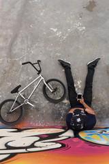 Man browsing phone sitting at bike