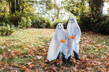 Two Kids in Ghost Costume Celebrating Halloween