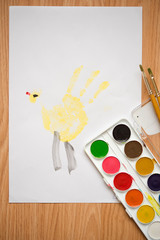 A trace by hand, a yellow duckling chicken, children's drawing with colored pencils and watercolors