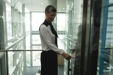 Businesswoman pressing a button in the elevator