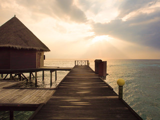 Perspective view of wooden pier and bungalow over the sea in sunset time at Maldives island for summer vacations holiday concept.
