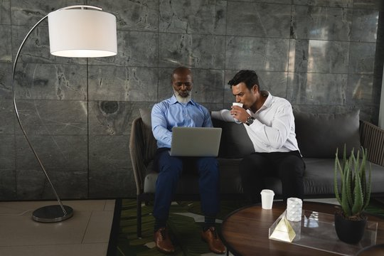 Businessmen having coffee and discussing over laptop