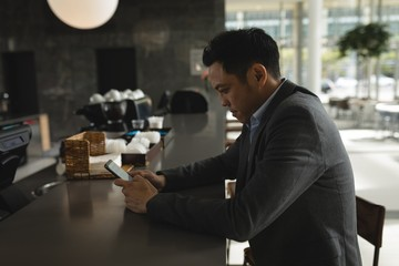 Businessman using his phone at the cafeteria counter