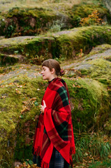 Young woman covered with bright woollen plaid surrounded by stonescovered with moss