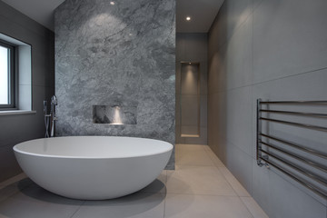 Contemporary freestanding bath tub standing in a grey bathroom.