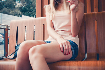 Close-up of the ideal legs of a young model. On the gentle hands of red nails. Girl in short attractive denim shorts. Low angle shooting