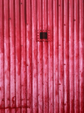 Bright red corrugated iron abstract exterior of building with small opening.